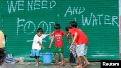 Các trẻ em trong thành phố Tacloban xách các thùng nước uống, 12/11/13