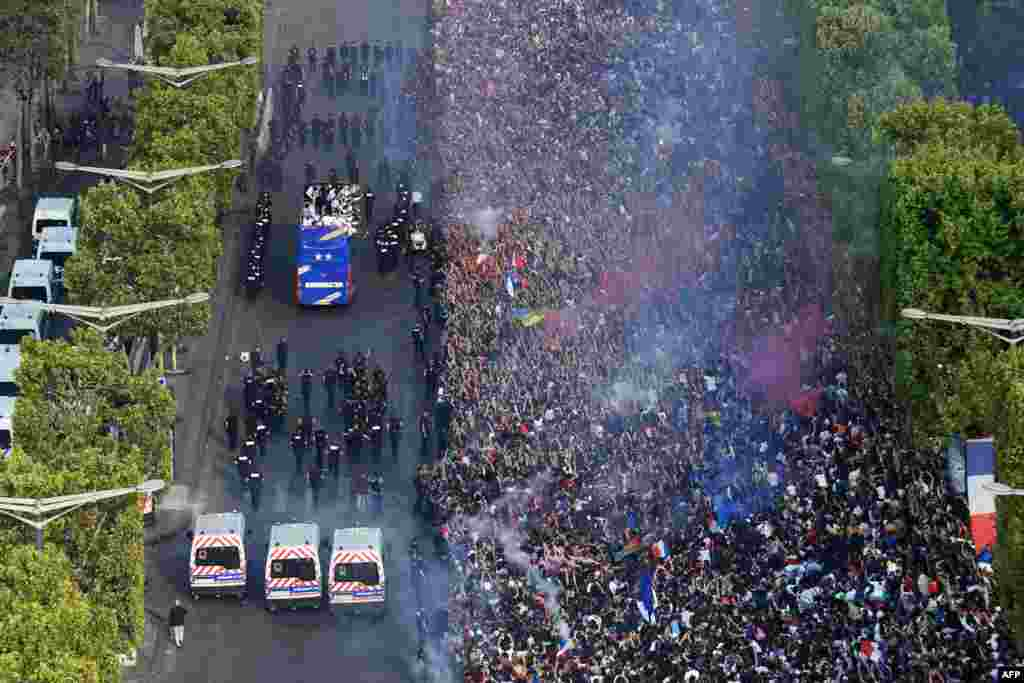 Fans greet France's national football team players as they celebrate on the roof of a bus while they parade down the Champs-Elysee avenue in Paris, after winning the Russia 2018 World Cup final football match.