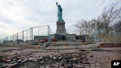 FILE - The Statue of Liberty stands beyond parts of a brick walkway damaged in Superstorm Sandy on Liberty Island in New York, Nov. 30, 2012. With scientists forecasting sea levels to rise by anywhere from several inches to several feet by 2100, historic structures and coastal heritage sites around the world are under threat.