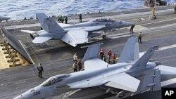 图为2010年美国FA-18战机准备从停靠在日本南部冲绳县的乔治华盛顿号航母上起飞资料照。