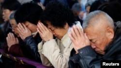 信众们在天津一个地下天主教堂祈祷(路透社)
