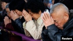Believers take part in a weekend Mass at an underground Catholic church in Tianjin.