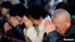 FILE - Believers take part in a weekend mass at an underground Catholic church in Tianjin, Nov. 10, 2013.