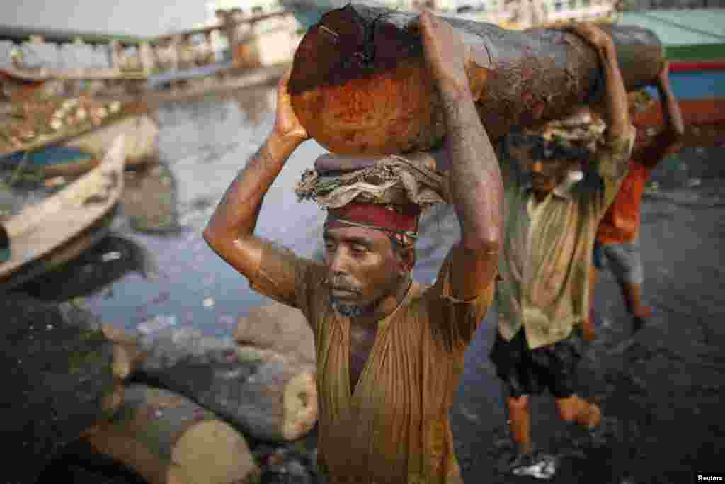 Workers carry a log at a timber factory by the river Buriganga in Dhaka, Bangladesh.