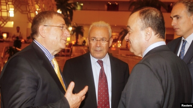 Members of the Syrian opposition chat with Nasser al-Qudwa, deputy to the Arab League and U.N. envoy to Syria, at the meeting of the General Assembly of the Syrian National Council, in Doha, Qatar, November 8, 2012.