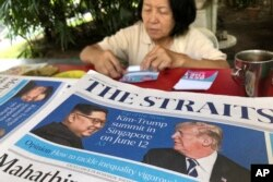 FILE - A news vendor counts her money near a stack of newspapers with a photo of U.S. President Donald Trump, right, and North Korea's leader Kim Jong Un on its front page on May 11, 2018, in Singapore.