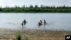 ماسکو سے 4660 کلو میٹر شمال مشرق میں قطب شمالی کے مرکزی حصے میں واقع قصبے ورخویانسک میں برف پگھلنے سے بننے والی جھیل میں بچے کھیل رہے ہیں۔ 21 جون 2020