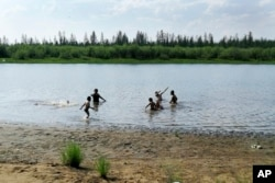 In this handout photo taken Sunday, June 21, 2020 and provided by Olga Burtseva, children play in the Krugloe lake outside Verkhoyansk, the Sakha Republic, about 4660 kilometers northeast of Moscow, Russia. (Olga Burtseva via AP)
