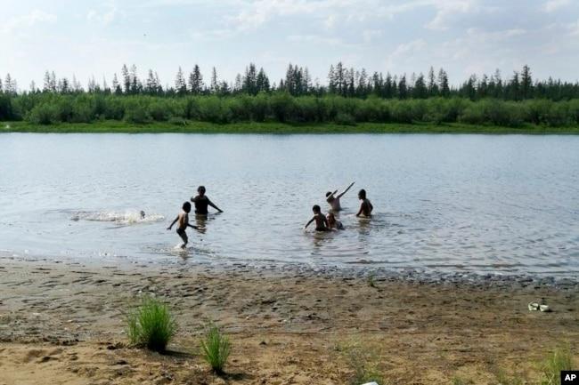 In this handout photo taken Sunday, June 21, 2020 and provided by Olga Burtseva, children play in the Krugloe lake outside Verkhoyansk, the Sakha Republic, about 4660 kilometers northeast of Moscow, Russia. (Olga Burtseva via AP)