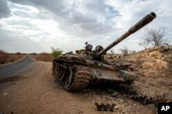 FILE - A destroyed tank is seen by the side of the road south of Humera, in an area of western Tigray annexed by the Amhara region during the ongoing conflict, in Ethiopia, May 1, 2021.