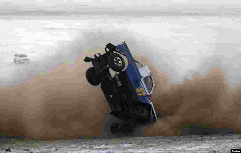 A car overturns during the Master Cross Race 2014 at Suuj Uul, outside Ulan Bator, Mongolia, Dec. 14, 2014.
