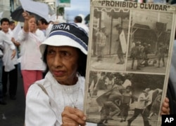 A woman holds up clipping of an old newspaper as she take part in a rally calling for former dictator Manuel Noriega to serve his prison sentence in Panama, in Panama City December 9, 2011.