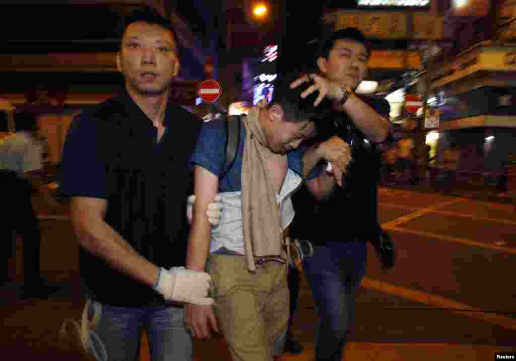 Policemen detain a pro-democracy demonstrator during a confrontation at Mong Kok shopping district in Hong Kong, early Nov. 26, 2014.