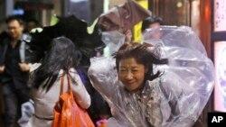 Warga Hong Kong menghadang angin kencang (15/9). (AP/Kin Cheung)