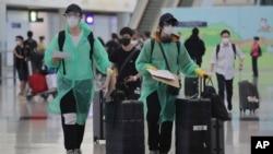 身穿防護服和戴口罩的旅客抵達香港國際機場。 (2020年3月23日)
