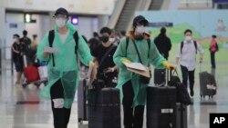 身穿防护服和戴口罩的旅客抵达香港国际机场。(2020年3月23日)