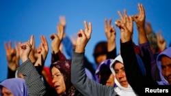 Suruç'ta Kobani'deki çatışmalarda ölen Kürt milislerin cenazesinde zafer işareti yapan Türkiyeli Kürt kadınlar