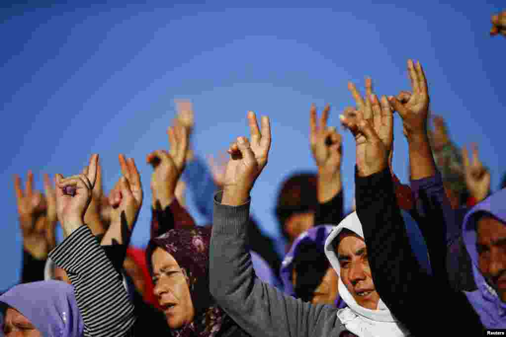 Turkish Kurdish women show victory sign during the funeral of Kurdish fighters at a cemetery in Suruc, Turkey, Oct. 21, 2014.