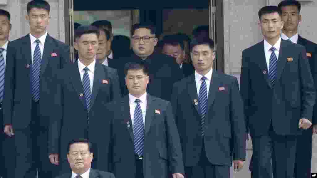 Kim Jong Un, arriba al centro, rodeado de guardaespaldas a la llegada a su lado de la Zona Desmilitarizada.