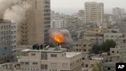 Asap dan kebakaran terlihat mengepul dari sebiah bangunan pencakar langit di kota Gaza (19/11). Serangan udara Israel atas wilayah ini sudah memasuki hari ke-6, sebagai upaya untuk menghentikan tembakan roket oleh kelompok Islamis Hamas.