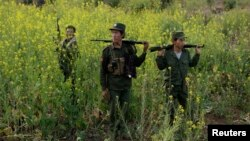 "Rebel soldiers of Myanmar National Democratic Alliance Army (MNDAA) patrol near a military base in Kokang region, March 10, 2015. Myanmar government forces have been battling rebels on the border with China since last month and China has urged Myanmar to ""lower the temperature."""