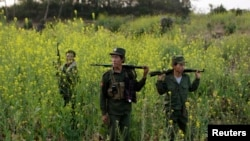 FILE - Rebel soldiers patrol near a military base in the Kokang region of Myanmar, March 10, 2015.