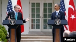 Turkish Prime Minister Recep Tayyip Erdogan, left, answers a question as he and U.S. President Barack Obama hold a joint news conference, White House Rose Garden, Washington, May 16, 2013.