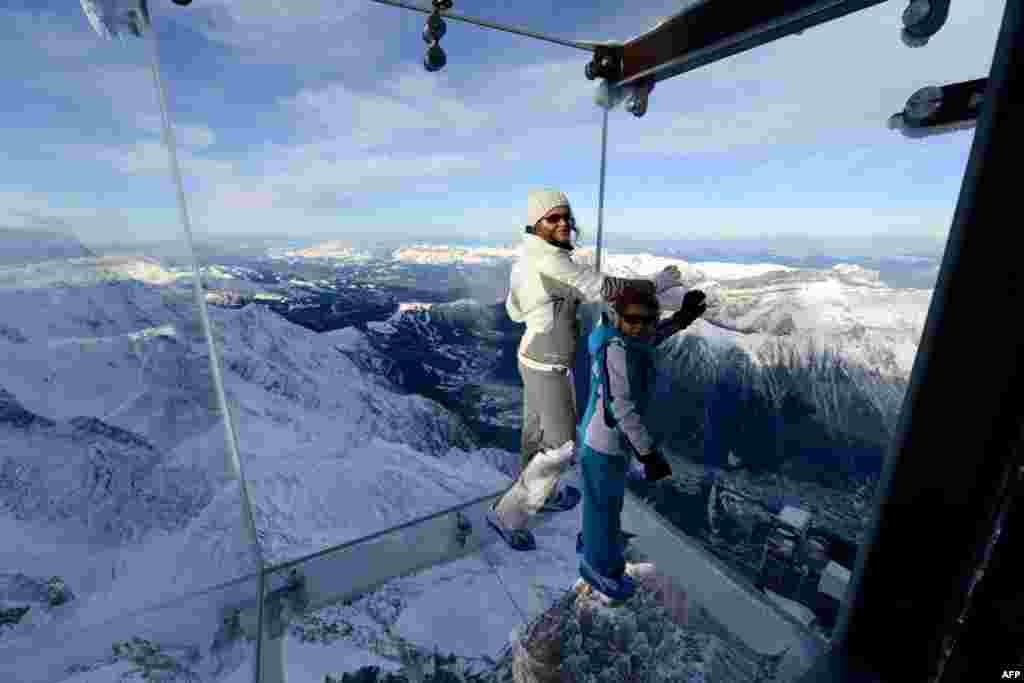 Seorang perempuan dan seorang anak berjalan di atas jembatan kaca (skywalk) sepanjang 1 kilometer, sambil menikmati pemandangan salah satu puncak pegunungan Alpen, yaitu puncak Chamonix, setinggi 3.842-meter di Perancis tenggara.