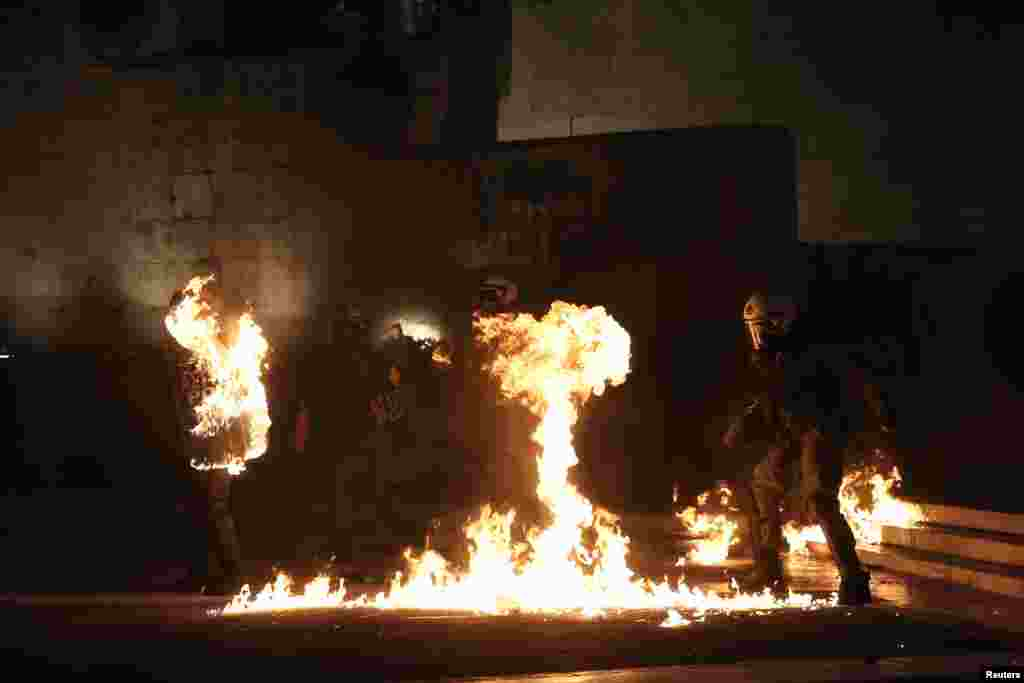 Maskirani demonstrant baca benzin bombu na specijalnom policijom ispred zgrade parlamenta, kao grčki zakonodavci glasati o najnovijoj rundi štednje, u Atini.