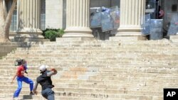 Students hurl stones on the University of the Witwatersrand campus in Johannesburg South Africa on Monday, Oct. 10, 2016.