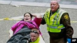 Una mujer es atendida por paramédicos en el sitio de las exposiones. La cifra oficial de heridos en los atentados al maratón de Boston es ahora de 264 heridos.