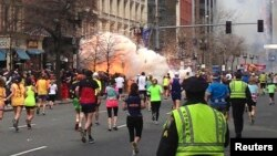 FILE- Runners continue to run towards the finish line of the Boston Marathon as an explosion erupts in this photo exclusively licensed to Reuters by photographer Dan Lampariello, in Boston, Massachusetts, April 15, 2013.