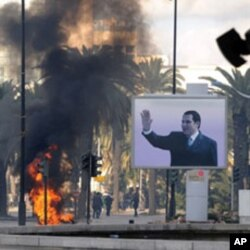 Smoke rises from fire left after clashes between security forces and demonstrators in Tunis, 14 Jan 2011