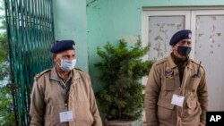 FILE - Indian police officials wear protective masks as they stand guard at an entrance of Himachal Pradesh Cricket Association.