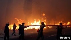Пожежники, солдати і місцеві мешканці намагаються зупинити вогонь поблизу Афін 23 липня 2018.