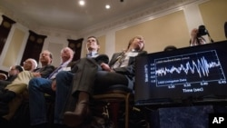 Audience members look at monitors displaying detected data which scientists say is proof of gravitational ripples, Thursday, Feb. 11, 2016, during a news conference at the National Press Club in Washington, just as Albert Einstein predicted a century ago.