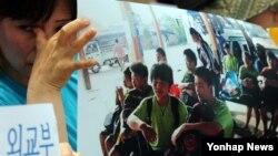 5일 한국 서울 외교부 청사 앞에서 시위를 벌이던 탈북민 고미화씨가 라오스에서 강제 북송된 청소년들의 사진을 든 채 눈물을 흘리고 있다.
