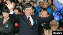 Nago City Mayor Susumu Inamine (C), flanked by his wife Ritsuko, celebrates after he was re-elected in the mayoral election in Nago, on the Japanese southern island of Okinawa, Jan. 19, 2014.