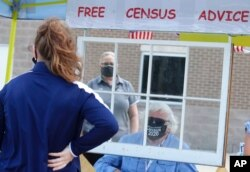 FILE - Amid concerns of the spread of COVID-19, census worker Ken Leonard wears a mask as he helps at a U.S. Census walk-up counting site set up for Hunt County in Greenville, Texas, July 31, 2020.