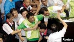 Anggota perlemen dari partai Demokrat (DPP) (mengenakan rompi hijau) terlibat perkelahian dengan anggota dari partai Nasionalis yang berkuasa (KMT) (mengenakan jaket hitam) di gedung legislatif, Taipei (2/8) sesaat sebelum pemungutan suara terkait referendum RUU pembangunan PLTN.