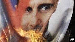 Xwenîşanderên Sûrî postereke Beşar Esed li ber Navenda Giştî ya Yekîtîya Ereb ya li Qahîreyê dişewtînin.