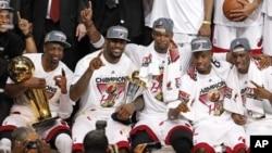 "Tim Miami Heat berpose bersama, sesaat setelah berhasil memenangkan Kejuaraan Liga NBA (22/6). Dwyane Wade (kiri) memegang Piala NBA ""Larry O'Brien"" dan LeBron James (dua dari kiri) memegang pialanya sebagai pemain terbaik NBA tahun ini."