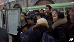 북한 장성택 전 국방위 부위원장이 처형된 다음날인 13일 북한 평양 시민들이 기차역에 게재된 신문을 읽고 있다.
