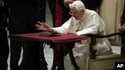 Pope Benedict XVI watches a tablet at the Vatican, in Rome, December 12, 2012.