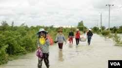 Villagers walk on a flooded road in Phnom Penh, Cambodia, on October 14, 2020. (Malis Tum/VOA Khmer)