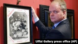 "Uffizi Gallery director Eike Schmidt holds up a copy of ""Vase of Flowers"" by Dutch artist Jan van Huysum, with writing in red reading ""Stolen."""