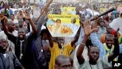 Les disciples de Cheikh Béthio Thioune chantent et portent les clubs sur un marchon le 17 mars 2012 à Dakar en soutien au président Abdoulaye Wade.