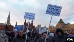 吞併克里米亞後,3月18日莫斯科紅場上官方組織的慶祝集會,參加者手舉標語:塞瓦斯托波爾,克里米亞,俄羅斯 。(美國之音白樺拍攝)