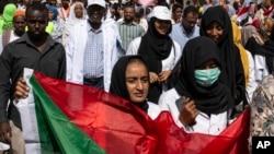 បាតុករម្នាក់កាន់ទង់ជាតិស៊ូដង់ នៅពេលស្រែកហ៊ោប្រឆាំងនឹងការកាន់អំណាចរបស់យោធា នៅទីលាន Armed Forces Square ក្នុងក្រុងខាទុំ (Khartoum) ប្រទេសស៊ូដង់ កាលពីថ្ងៃទី២៨ ខែមេសា ឆ្នាំ២០១៩។