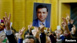 FILE - A supporter holds a portrait of Selahattin Demirtas, detained leader of Turkey's pro-Kurdish opposition Peoples' Democratic Party at a meeting at the Turkish parliament in Ankara.